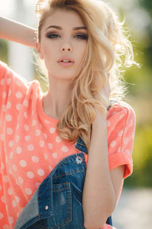 outdoor glamour: Summer portrait of a beautiful woman. Very beautiful blonde girl with big brown eyes bushy long hair dressed in a pink Tshirt with white polka dots and denim overalls in dark blue green park resting in a sunny summer day Stock Photo