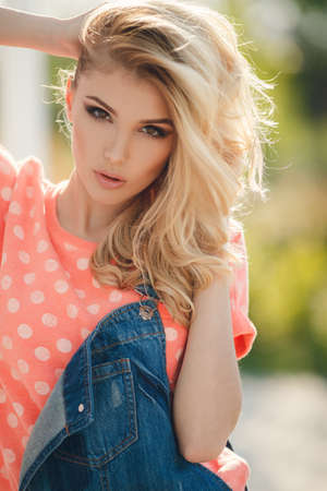 beautiful blonde girl with green eyes: Summer portrait of a beautiful woman. Very beautiful blonde girl with big brown eyes bushy long hair dressed in a pink Tshirt with white polka dots and denim overalls in dark blue green park resting in a sunny summer day Stock Photo