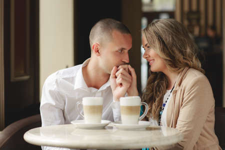 cafe: Beautiful young couple womanbrunette with lush curly hair and beautiful smile is dressed in a beige jacket and a young mana brunette with short hair wearing a white shirt spend time in the cozy town for a Cup of coffee lattetalking about love Stock Photo