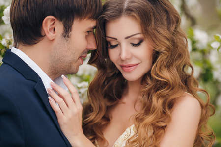 Wedding couplethe groom is a young darkhaired man in a black suit and pink bow tiebeautiful bridebrunette with long curly hair in a white wedding dress on her head a wreathposing embracing in the Park among the blooming trees. photo