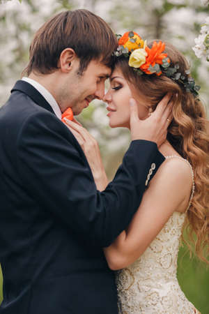 groom and bride: Wedding couplethe groom is a young darkhaired man in a black suit and pink bow tiebeautiful bridebrunette with long curly hair in a white wedding dress on her head a wreathposing embracing in the Park among the blooming trees.