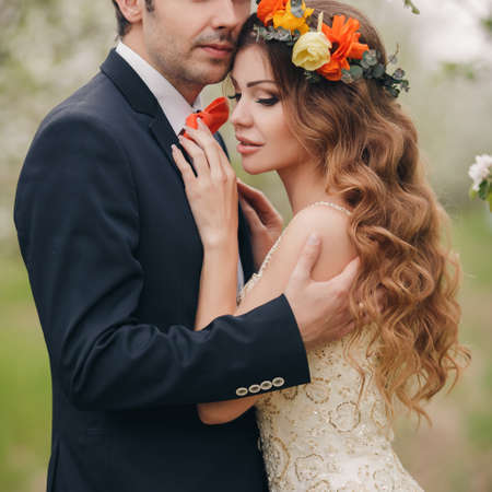 Wedding couplethe groom is a young darkhaired man in a black suit and pink bow tiebeautiful bridebrunette with long curly hair in a white wedding dress on her head a wreathposing embracing in the Park among the blooming trees.