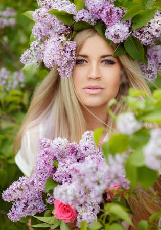 Beautiful smiling girl with long blonde straight hair resting the spring at a Park near the Bush blossoming lilac with a fashion makeover wearing a beautiful wreath of flowers in her hands a beautiful lilac bouquet photo