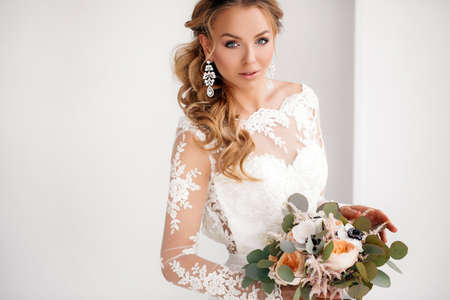 nude bride: Young attractive bride with a wedding bouquet.Wedding portrait of happy blueeyed bride with long curly hairbeautiful smilemakeupwhite wedding dressearrings in your earsholding a large bouquet of beautiful natural roses delicate cream color Stock Photo