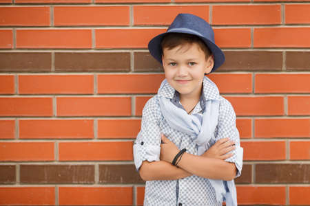 head collar: Stylish boybrunette with short hair on his head wearing a fashionable hat in dark greywearing a plaid light shirt on the neck under the shirt collar wearing a light grey scarfbaby posing on the street against the red brick wall in the summer