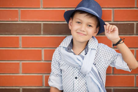 the lovely boy: Stylish boybrunette with short hair on his head wearing a fashionable hat in dark greywearing a plaid light shirt on the neck under the shirt collar wearing a light grey scarfbaby posing on the street against the red brick wall in the summer