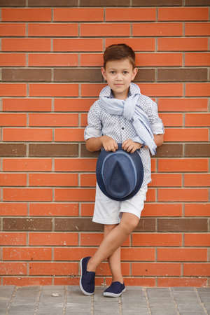stylish boy: Stylish boybrunette with short hair on his head wearing a fashionable hat in dark greywearing a plaid light shirt on the neck under the shirt collar wearing a light grey scarfbaby posing on the street against the red brick wall in the summer