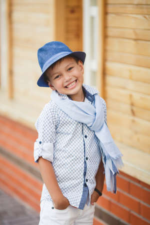 head collar: Stylish boybrunette with short hair on his head wearing a fashionable hat in dark greywearing a plaid light shirt on the neck under the shirt collar wearing a light grey scarfbaby poses on the background of a wooden house in the summer Stock Photo