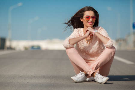 pretty young girl: Beautiful brunette with model looks long hairbeautiful smile and white teethpink glassesdressed in a pink summer sweater and pink jeanson the hand wears a watch in whiteon her neck is a necklacesits on the road in the city