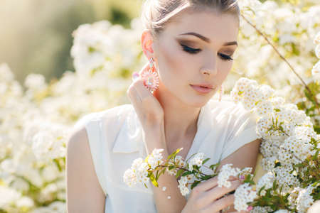 Young beautiful woman brunette hair is tied in her hairbig brown eyesstylish makeup in the ears earrings pinkdressed in a white sleeveless blouseposing in spring Parknext to a blossoming white flowers Bush