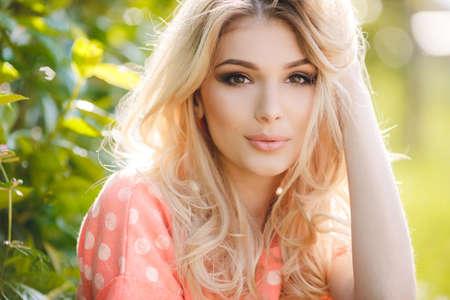 Summer portrait of a beautiful woman.Very beautiful blonde girl with big brown eyes bushy long hair dressed in a pink Tshirt with white polka dots and denim overalls in dark blue green park resting in a sunny summer day