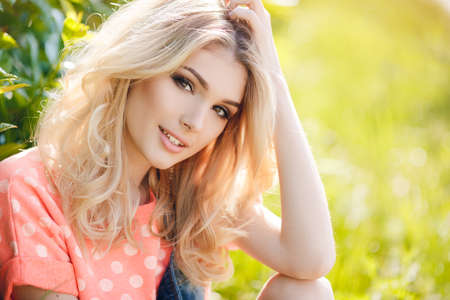 outdoor glamour: Summer portrait of a beautiful woman.Very beautiful blonde girl with big brown eyes bushy long hair dressed in a pink Tshirt with white polka dots and denim overalls in dark blue green park resting in a sunny summer day