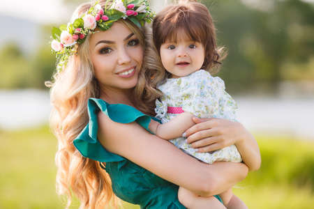 Young beautiful mother modelblonde with lush long hairbeautiful makeupon her head a wreath of flowers plays on a green meadow in summer with a young daughtera girl with brown eyes and luxuriant hairSunny day photo