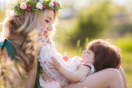 luxuriant: Young beautiful mother modelblonde with lush long hairbeautiful makeupon her head a wreath of flowers plays on a green meadow in summer with a young daughtera girl with brown eyes and luxuriant hairSunny day