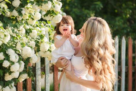 weisse kleider: Portrait der gl�cklichen Frau mit einer kleinen Tochter in einer Ortschaft in der spring.Happy Mutter mit ihrer kleinen Tochter in ihrem armsstanding gegen den Zaun neben einem bl�henden wei�en Blumen des Bush in einer Ortschaft in summer wei�en Kleidern