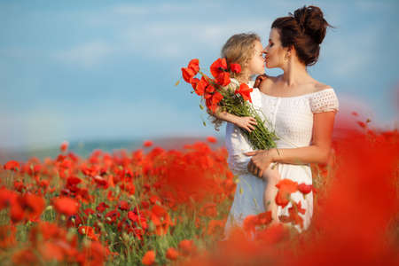 Young mother brunette with fashionable hairstyle, dressed in a white dress is holding her little daughter, a girl with blond, long curly hair wearing a white dress, walking together on a blossoming red poppies field in early summer