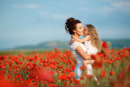 poppies: Young mother brunette with fashionable hairstyle, dressed in a white dress is holding her little daughter, a girl with blond, long curly hair wearing a white dress, walking together on a blossoming red poppies field in early summer