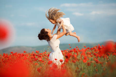 red poppies on green field: Young mother brunette with fashionable hairstyle, dressed in a white dress is holding her little daughter, a girl with blond, long curly hair wearing a white dress, walking together on a blossoming red poppies field in early summer