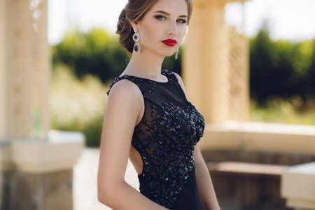 All'aperto foto di moda di bella donna sensuale in abito lussuoso posa paillettes nel parco di estate. Foto di moda della bella donna di gara con i capelli scuri in posa elegante abito in giardino estivo