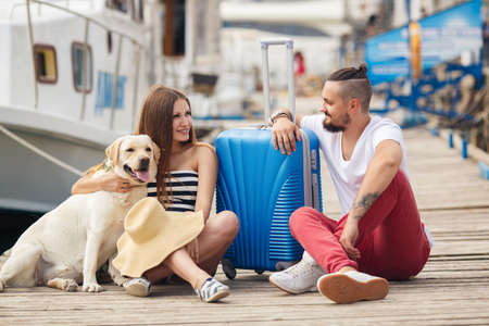 A young married couple, a man with a beard and a pregnant woman, brunette, long straight hair, with a friend, a Labrador dog, awaiting departure on a journey, sitting on the dock with a big blue suitcase waiting for the ship Archivio Fotografico