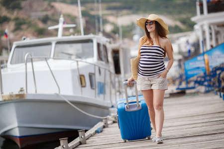 Jonge zwangere vrouw, brunette, lang steil haar, het dragen van een zonnebril en een strooien hoed, in een korte gestreepte jurk, wacht op de boot, zittend op de pier in de buurt van de zee met een rieten mand, die naast een koffer met wielen blauw Stockfoto