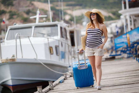 woman looking: Young pregnant woman, brunette, long straight hair, wearing sun glasses and a straw hat, in a short striped dress, waits for the boat, sitting on the pier near the sea with a straw basket, standing next to a suitcase with wheels blue