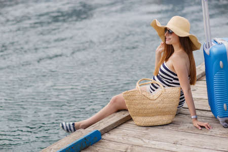 Young pregnant woman, brunette, long straight hair, wearing sun glasses and a straw hat, in a short striped dress, waits for the boat, sitting on the pier near the sea with a straw basket, standing next to a suitcase with wheels blue