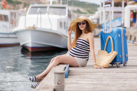 waits: Young pregnant woman, brunette, long straight hair, wearing sun glasses and a straw hat, in a short striped dress, waits for the boat, sitting on the pier near the sea with a straw basket, standing next to a suitcase with wheels blue