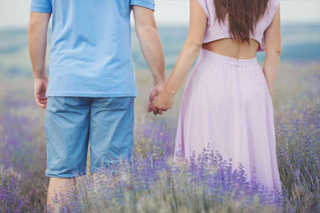 intoxicating: romantic young couple, a man and a woman during summer vacation spending time in the lavender fields in Provence, southern France, recognized each other in love, flowers, hands, arms, the intoxicating scent of flowers.