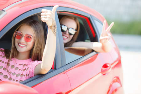 Two happy young girlfriends traveling in the car. Two beautiful young girl with a sweet smile, sun glasses, travel in a pink car in the summer, opening the car window showing thumbs up sign of victory and joy.
