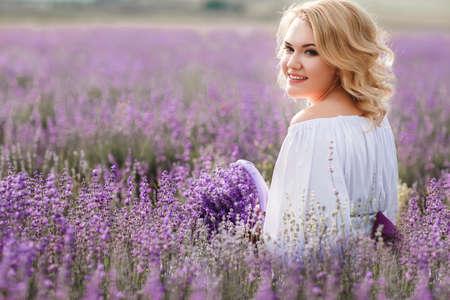 ラベンダー畑の美しい花嫁。ラベンダーの花の新婚女性。屋外のウェディング ドレスの若い女性。小さな籐のバスケットとラベンダー畑でポーズを