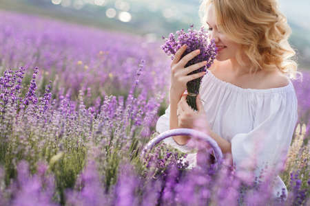lavender: Beautiful Bride in lavender field. Newlywed woman in lavender flowers.Young woman in wedding dress outdoors. Beautiful young woman in white dress posing in a lavender field with small wicker basket