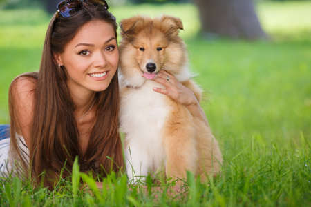 green clothes: woman beautiful young happy with long dark hair in striped sweater holding collie dog. Young woman playing with Collie puppy outdoors in the park. Stock Photo