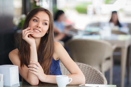 sitting pretty: pretty young woman sitting in cafe with a cup of tea or coffee outdoor. Charming woman in a restaurant. Woman with coffee Stock Photo