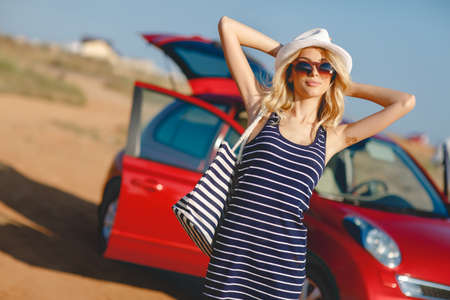 woman street: Summer vacation. Car trip. Travelling. Car travel. By the sea. Beautiful blonde woman standing with red small car on the background. Sea style. Summer vacation car road trip freedom concept.