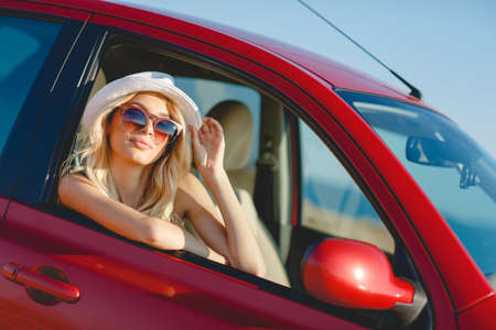 happyness: blonde beautiful woman in sunglasses and white hat sitting in red car by the sea. Sea view. Vacation concept. Happyness. Freedom. road trip on beautiful sunny summer day