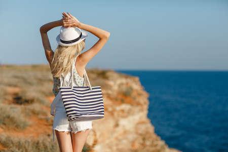 夏帽子とビーチで金髪女性バッグ バイ ザ シーの岩の端に立っています。海の景色。自由。風。夏。休暇。ヨガ。空と海を探しています。楽しみに