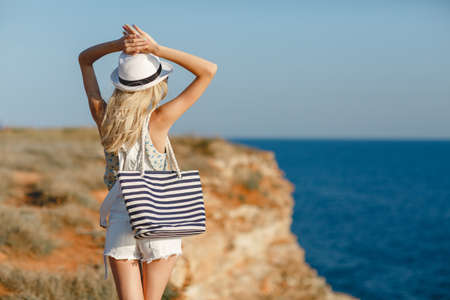 Blonde woman in summer hat and beach bag standing on the edge of the rock by the sea. Sea view. Freedom. Wind. Summer. Vacation. Yoga. looking to a sky and sea. Looking forward