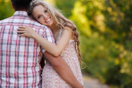 若い幸せな家族。男は、妊娠中の女性の幸せな性質。外の芝生の上に座って彼の夫と幸せな美しい妊娠中の女性。夏のパークで家族一緒に。女性が