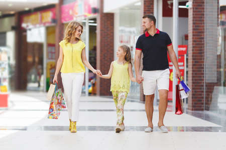 Mother, daughter and father in shopping mall. Family with shopping bags having fun smiling. Man, woman and child go on shopping. Stock Photo