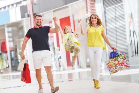 plaza comercial: Madre, hija y padre en el centro comercial. Familia con bolsas de la compra que se divierten sonriendo. Hombre, mujer y niño van a las compras.
