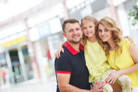 one family: Mother, daughter and father in shopping mall. Family with shopping bags having fun smiling. Man, woman and child go on shopping. Stock Photo