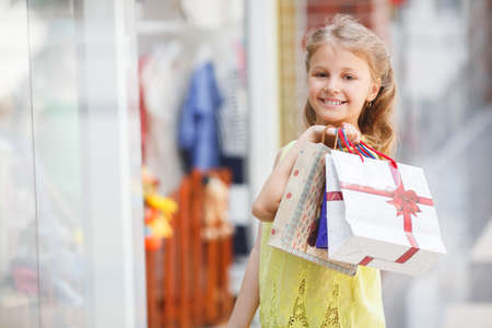without windows: Smiling little girl with shopping bags in a large supermarket.Preschool age girl, blonde with curly hair in a city supermarket with paper bags, treats and shop windows, one without parents, wearing a light blouse and trousers Stock Photo