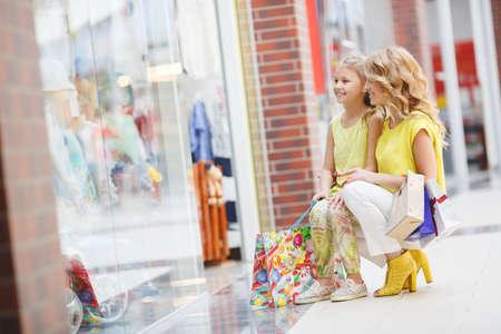 ni�os de compras: Joven madre y su hija va de compras juntos, la mujer con el ni�o en las compras en el centro comercial con bolsas, la joven familia que est� gastando alegremente tiempo para hacer compras en gran encanto Foto de archivo