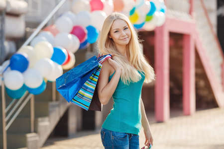 fashionable female: Pretty woman shopping at the mall on a sunny day, the young woman with a beautiful figure and a long fair hair, in a green undershirt and blue jeans, holds multi-colored bags in hand, goes to do shopping to shopping center of the big city