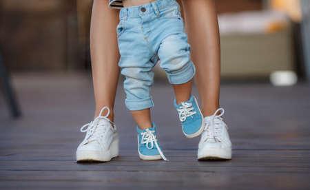 manos y pies: Los primeros pasos del niño, mamá en zapatillas de deporte blancas con un hijo pequeño, vestido con pantalón azul y zapatos de color azul, un cálido día de verano y aprender a caminar en la calle, los primeros pasos, la madre sostiene a su hijo.