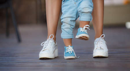 maintains: The first steps of the kid, Mom in white sneakers with a young son, dressed in blue pants and blue shoes, a warm summer day and learn to walk in the street, the first steps, the mother maintains her son.