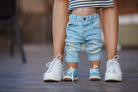 The first steps of the kid, Mom in white sneakers with a young son, dressed in blue pants and blue shoes, a warm summer day and learn to walk in the street, the first steps, the mother maintains her son.