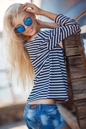 flirtatious: Beautiful young woman with long blonde straight hair, sunglasses with blue glasses, shorts and a striped shirt sailor, spends time in the dock, repair facilities boats
