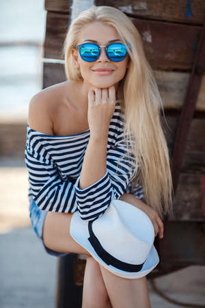 Beautiful young woman with long blonde straight hair, sunglasses with blue glasses, shorts and a striped shirt sailor, spends time in the dock, repair facilities boats